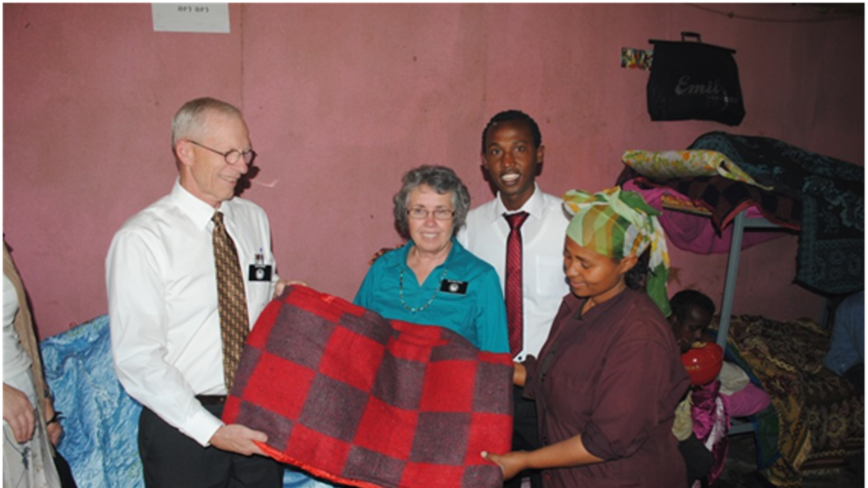 """Chewy with Clyde and Dolores Moses present blankets to Facility Director Manio Tadesse"